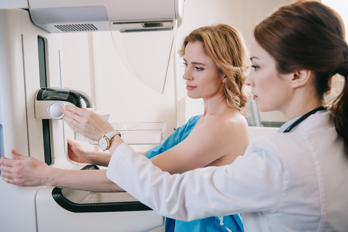 attentive radiographer adjusting x-ray machine for mammography test while standing near patient